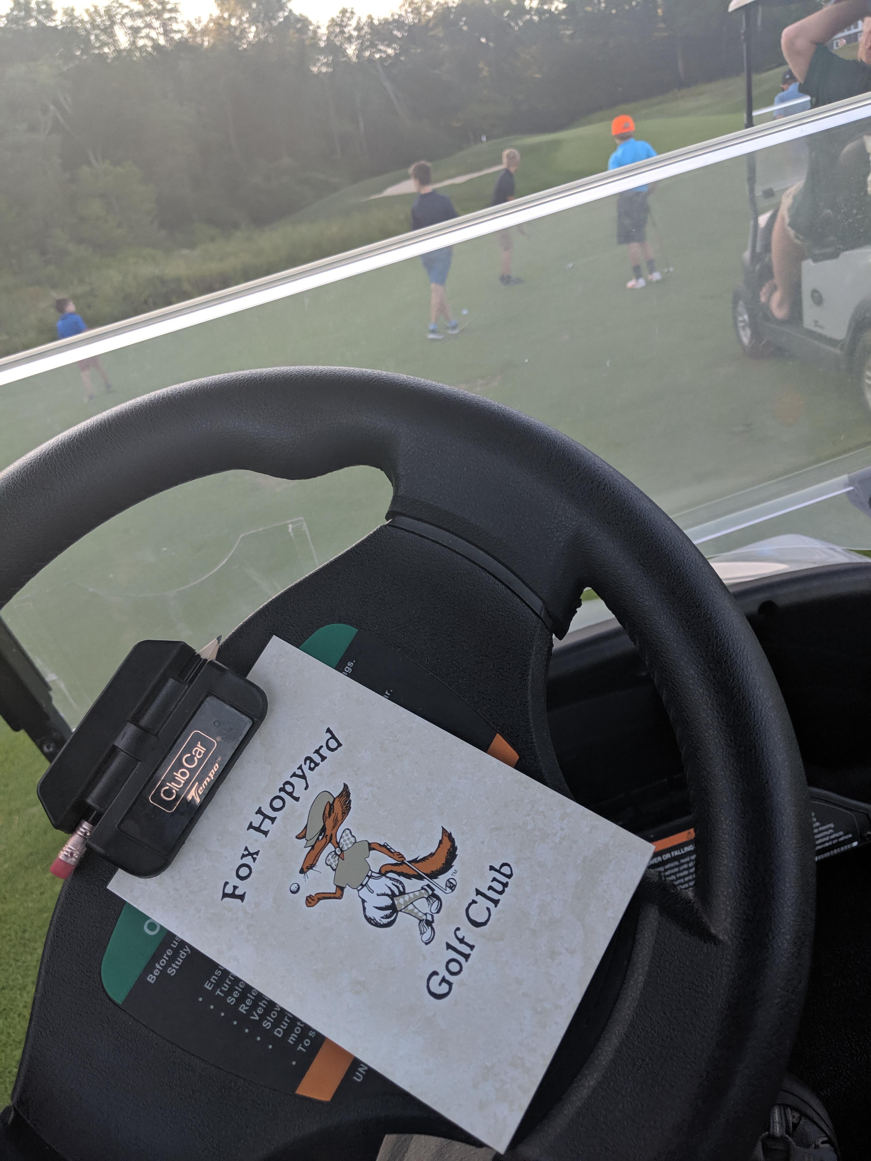 placard on steering wheel of golf cart